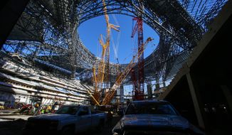 In this photo taken Friday, Dec. 2, 2016, construction of the new Mercedes Benz Stadium for the Atlanta Falcons continues in Atlanta. The Georgia Dome, which in 1992 became the Atlanta Falcons' home, also has been home to Georgia State football, high school state championships, Peach Bowls and SEC championship games, two Super Bowls and three Final Fours, will make way for the new Mercedes Benz Stadium. (AP Photo/Butch Dill)