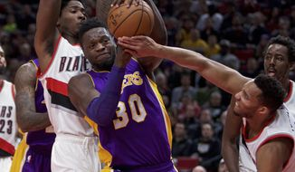 Los Angeles Lakers forward Julius Randle (30) keeps the ball away from Portland Trail Blazers guard Evan Turner, right, and forward Ed Davis, left, during the first half of an NBA basketball game in Portland, Ore., Thursday, Jan. 5, 2017. (AP Photo/Craig Mitchelldyer)