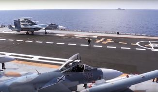 FILE - In this file photo made from the footage taken from Russian Defense Ministry official web site on Tuesday, Nov. 15, 2016, Russian Su-33 fighter jets stand on the flight deck of the Admiral Kuznetsov aircraft carrier in the eastern Mediterranean Sea. Russia says it is withdrawing the Admiral Kuznetsov aircraft carrier and some other warships from the waters off Syria as the first step in drawing down forces in Syria. (Russian Defense Ministry Press Service/ Photo via AP, File)