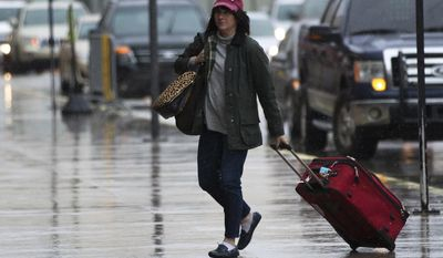 A traveler arrives at Hartsfield-Jackson Atlanta International Airport as it begins to rain, Friday, Jan. 6, 2017, in Atlanta. Shoppers emptied shelves of bread and milk, road workers began working 12-hour shifts, and states of emergency were declared in Alabama, Georgia and the Carolinas ahead of a winter storm stalking the South.(Branden Camp/Atlanta Journal-Constitution via AP)