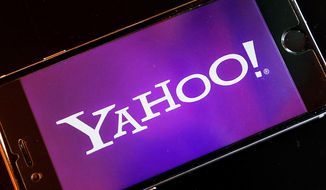 FILE - In this Dec. 15, 2016, file photo, the logo of Yahoo appears on a smartphone in Frankfurt, Germany. Yahoo Finance deleted a tweet that accidentally included a racial epithet Thursday, Jan. 5, 2017. (AP Photo/Michael Probst, File)