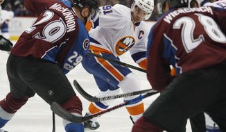 New York Islanders center John Tavares, center, drops back to defend as Colorado Avalanche center Nathan MacKinnon, front left, tries to pass the puck to defenseman Patrick Wiercioch in the second period of an NHL hockey game Friday, Jan. 6, 2017, in Denver. (AP Photo/David Zalubowski)