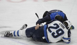 Winnipeg Jets forward Patrik Laine (29) is helped by a trainer after getting hit during the third period of an NHL hockey game against the Buffalo Sabres, Saturday, Jan. 7, 2017, in Buffalo, N.Y. (AP Photo/Jeffrey T. Barnes)