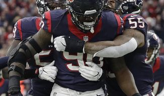 Houston Texans defensive end Jadeveon Clowney (90) is congratulated after making an interception against the Oakland Raiders during the first half of an AFC Wild Card NFL football game Saturday, Jan. 7, 2017, in Houston. (AP Photo/Eric Gay)