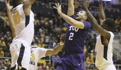 TCU guard Michael Williams (2) drives to the basket as West Virginia forward Sagaba Konate (50) attempts to block his shot during the first half of an NCAA college basketball game, Saturday, Jan. 7, 2017, in Morgantown, W.Va. (AP Photo/Raymond Thompson)