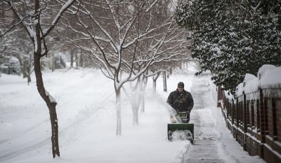Daniel Mitchell operates a snowblower along the sidewalk on Norfolk Ave. next to Randolph College on Saturday, Jan. 7, 2017 in Lynchburg, Va. (Jay Westcott  /News & Daily Advance via AP)