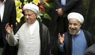 In this Aug. 4, 2013, file photo, Iranian President Hassan Rouhani, right, and former President Akbar Hashemi Rafsanjani, wave, as they arrive for Rouhani's swearing-in ceremony at the parliament, in Tehran, Iran. Iranian state media said Sunday, Jan. 8, 2017, that Rafsanjani has died at age 82 after having been hospitalized because of a heart condition. Rafsanjani, who served as president from 1989 to 1997, was a leading politician who often played kingmaker in the country's turbulent politics. He supported President Rouhani. (AP Photo/Ebrahim Noroozi, File)