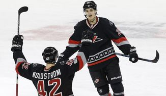Carolina Hurricanes' Joakim Nordstrom (42), of Sweden, congratulates Sebastian Aho, of Finland, following Aho's game winning goal against the Boston Bruins during overtime in an NHL hockey game in Raleigh, N.C., Sunday, Jan. 8, 2017. Carolina won 4-3. (AP Photo/Gerry Broome)