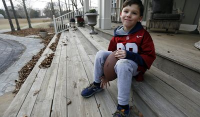 In this Friday, Jan. 6, 2017 photo, Boone Murphree, 8, poses as he rests after a receiving and punting workout, Friday, Jan. 6, 2017, outside his grandparents home in Tupelo, Miss., shares an unusual bond with his friend, Alabama kicker Adam Griffith. The two are originally from Poland, they lived for a while in an orphanage and both were adopted by Southern families. The two first met at Alabama's 2015 spring football game and have established a friendship that Murphree takes seriously. Boone, an ardent 'Bama fan, constantly wears an Alabama jersey with Griffith's name and number on it and sees himself as a eventual linebacker and punter for the Crimson Tide. (AP Photo/Rogelio V. Solis)