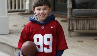 In this Friday, Jan. 6, 2017 photo, Boone Murphree, 8, poses after an afternoon of punting and passing the football with his family, Friday, Jan. 6, 2017, in Tupelo, Miss., shares unusual bonds with Alabama kicker Adam Griffith besides football. They are originally from Poland, they lived for a while in an orphanage and both were adopted by Southern families.The two met at Alabama's 2015 spring football game and established a friendship that Murphree takes seriously. (AP Photo/Rogelio V. Solis)
