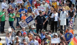 FILE - In this April 25, 2016 file photo, protesters head to the legislative building in Raleigh, N.C., for a sit-in against House Bill 2, a contentious law that limited protections for LGBT people. After a string of major gains in recent years, LGBT activists are bracing for a different task in 2017 - trying to prevent Republicans in Congress and state legislatures from undermining those gains. (Chuck Liddy/The News & Observer via AP, File)