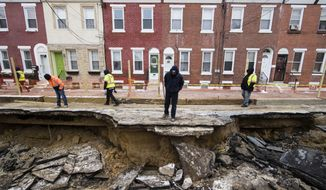 Workers inspect a sinkhole in Philadelphia, Monday, Jan. 9, 2017. The Philadelphia Water Department said a water main break caused the sinkhole to open up on the street. (AP Photo/Matt Rourke)