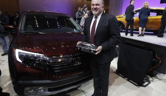 President and CEO of Honda North America John Mendel stands next to the Honda Ridgeline after winning the truck of the year at the North American International Auto show, Monday, Jan. 9, 2017, in Detroit. (AP Photo/Carlos Osorio)