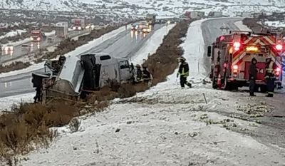 In this photo, made available by the Colorado Department of Transportation, a fire crew responds Monday, Jan. 9, 2017, at the scene of an overturned diesel tanker truck involved in a high wind-related accident, with the tanker spilling about 2000 gallons of diesel, along Interstate 70 near Gypsum, in western Colo. High winds have overturned some large vehicles and damaged buildings in the Colorado Springs area while ice is making travel dangerous in western Colorado. (Randy McIntosh/CDOT via AP)
