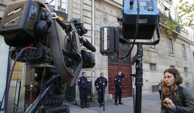 FILE - In this Oct.3, 2016 file photo, French police officers and a TV crew stand outside the residence of Kim Kardashian West in Paris. Police in Paris say Monday Jan.9, 2017 that 16 people have been arrested in connection with the October theft of more than $10 million worth of jewelry from Kim Kardashian West. (AP Photo/Michel Euler, File)
