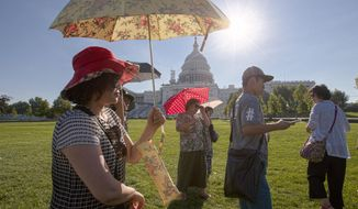 FILE - In this Aug. 12, 2016 file photo, visitors from Korea shield themselves from the early morning sun as they tour the Capitol in Washington, with temperatures lingering in upper 90s. (AP Photo/J. Scott Applewhite, File)