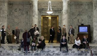 FILE - In this March 9, 2016 file photo, lobbyists and other observers wait outside the Senate chamber at the Capitol in Olympia, Wash. Lawmakers will begin the 2017 legislative session Monday, Jan. 9, 2017, with few Capitol watchers expecting that they'll finish this year's 105-day legislative session on time as they wrestle with the final piece of a court mandate on education funding. (AP Photo/Ted S. Warren, file)