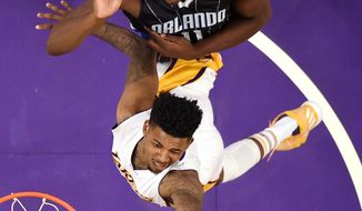 Los Angeles Lakers guard Nick Young, bottom, shoots as Orlando Magic center Bismack Biyombo, of the Republic of Congo, defends during the first half of an NBA basketball game, Sunday, Jan. 8, 2017, in Los Angeles. (AP Photo/Mark J. Terrill)