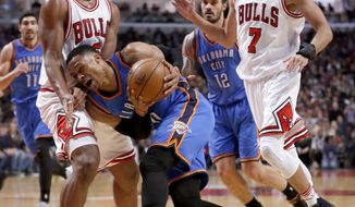 Oklahoma City Thunder's Russell Westbrook, center, drives on Chicago Bulls' Cristiano Felicio, left, as Steven Adams (12) and Michael Carter-Williams (7) watch during the first half of an NBA basketball game Monday, Jan. 9, 2017, in Chicago. (AP Photo/Charles Rex Arbogast)