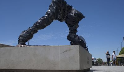 The severed statue of soccer star Lionel Messi is seen covered in Buenos Aires, Argentina, Tuesday, Jan. 10, 2017. The city government reported Monday night Messi's statue was destroyed and said they are already working on repairing it.(AP Photo/Natacha Pisarenko)