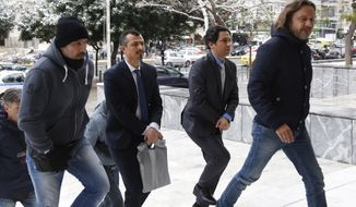 Handcuffed Turkish military officers, center, are escorted by plain-clothed police officers as they arrive at the Supreme Court in Athens, on Tuesday, Jan. 10, 2017. A prosecutor at Greece's Supreme Court recommended on Tuesday the court reject an extradition request for the first two of eight Turkish servicemen who fled to Greece after a failed July military coup in their country. (Stelios Misinas/Eurokinissi via AP)