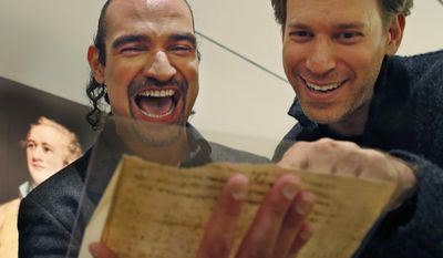"""Javier Munoz, left, who plays Alexander Hamilton in the enormously popular Broadway hip-hop musical """"Hamilton,"""" laughs with the show's set designer David Korins as they read a letter from Hamilton to an unnamed recipient, possibly Jeremiah Wadsworth, about the 1796 presidential election, Tuesday, Jan. 10, 2017, at Sotheby's auction house in New York. This and a trove of artifacts related to Alexander Hamilton, including love letters to his wife, Eliza, will be offered up for auction at Sotheby's Jan. 18, part of """"Americana week."""" Munoz says holding and reading Hamilton's private thoughts about everything from his love life to war in America will have a deep effect on his Broadway performance. (AP Photo/Kathy Willens)"""