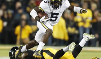 FILE - In this Nov. 12, 2016, file photo, Michigan's Jabrill Peppers (5) breaks a tackle by Iowa defensive back Desmond King, rear, during the first half of an NCAA college football game, in Iowa City, Iowa. Peppers has decided to enter the NFL draft, skipping his senior season at Michigan. The Heisman Trophy finalist announced his plans Tuesday, Jan. 10, 2017. The 6-foot-1, 205-pound Peppers is projected to be a first-round pick in April.  (AP Photo/Charlie Neibergall, File)