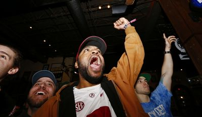 Alabama fans Myles Pasley, center, of Nashville, Tenn., and Michael Mumpower, left, of Montgomery, Ala., acheer after Alabama scored a touchdown against Clemson, as fans watched television coverage of  the NCAA college playoff championship football game, Monday, Jan. 9, 2017, in Tuscaloosa, Ala. (AP Photo/Brynn Anderson)