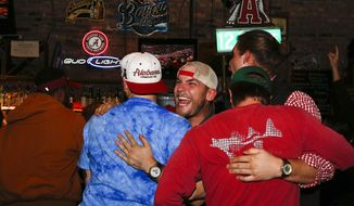 Alabama fans Calvin Ganus, center, of Tuscaloosa, Ala., celebrates with Daniel Chisum, of Holtville, Ala., after Alabama scored a touchdown, as they watched television coverage of the NCAA college playoff championship football game between Alabama and Clemson, Monday, Jan. 9, 2017, in Tuscaloosa, Ala. (AP Photo/Brynn Anderson)