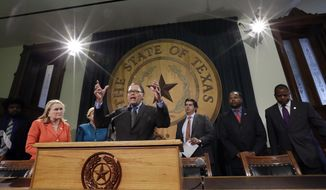 Sen. Jose Rodriguez, D-El Paso, center, stands with other Texas legislators and civil rights representatives during a news conference at the Texas Capitol, Monday, Jan. 9, 2017, in Austin, Texas. Rodriguez and the group called for Texas Gov. Greg Abbott and other legislators to protect the rights of minorities and immigrants as the Texas' 85th Legislative session begins Tuesday. (AP Photo/Eric Gay)