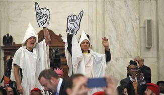 Demonstrators are seen on Capitol Hill in Washington, Tuesday, Jan. 10, 2017, during the Senate Judiciary Committee's confirmation hearing for Attorney General-designate, Sen. Jeff Sessions, R-Ala. (AP Photo/Andrew Harnik)