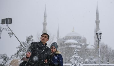 In this photo taken on Monday, Jan. 9, 2017, a couple takes a selfie at Sultanahmet district, one of Istanbul's main tourist attractions. TThese days, with a string of terror attacks targeting Istanbul still fresh in his memory, some residents say they are adapting their daily routines because of fears they could become the latest victims of violent extremism. (AP Photo/ Emrah Gurel)