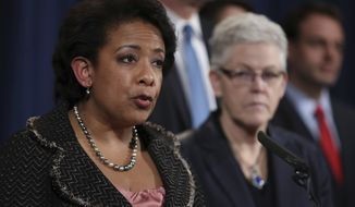Attorney General Loretta Lynch, accompanied by Environmental Protection Agency Administrator Gina McCarthy, right, and others, speaks during a news conference at the Justice Department in Washington, Wednesday, Jan. 11, 2017, to discuss Volkswagen emissions. Six high-level Volkswagen employees have been indicted by a grand jury in the company's diesel emissions cheating scandal, as the company admitted wrongdoing and agreed to pay a record $4.3 billion penalty. (AP Photo/Manuel Balce Ceneta)