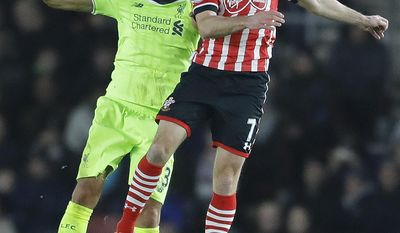 Southampton's Shane Long, right, and Liverpool's Mamadou Sakho challenge for the ball during the English League Cup semifinal first leg soccer match between Southampton and Liverpool at St. Mary's stadium in Southampton, England, Wednesday, Jan. 11, 2017.(AP Photo/Frank Augstein)