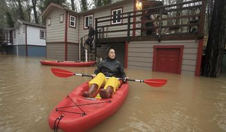 Elizabeth Hamilton, a Resident of Sycamore Court Apartments, keeps an eye on floodwaters as she and another resident ask others if they need a lift out of the floodwaters in Guerneville, Calif., Tuesday, Jan. 10, 2017. About 2,000 people in a rural California community near Sacramento were asked to leave their homes Tuesday as a river swollen by days of heavy rain threatened to flood, while north of San Francisco thousands more were urged to seek higher ground. (Kent Porter/The Press Democrat via AP)