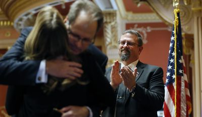 Incoming Colorado State Senate President Kevin Grantham, R-Canon City, right, applauds as outgoing Colorado State Senate President Bill Cadman, R-Colorado Springs, hugs his wife Lisa after Cadman gave his farewell speech in Senate chambers, during the opening session of the 2017 Colorado Legislature, at the Capitol, in Denver, Wednesday Jan. 11, 2017. The Colorado Democratic House and Republican Senate are waiting for cues from Washington and from Democratic Gov. John Hickenlooper about the priorities this year. (AP Photo/Brennan Linsley)