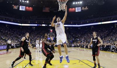 Golden State Warriors' Zaza Pachulia (27) drives to the basket past Miami Heat's Luke Babbitt, left, Hassan Whiteside, center, and Goran Dragic, right, during the first half of an NBA basketball game Tuesday, Jan. 10, 2017, in Oakland, Calif. (AP Photo/Marcio Jose Sanchez)