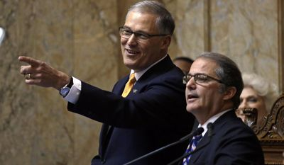 Gov. Jay Inslee, left, looks toward the House floor with outgoing Lt. Gov. Brad Owen before Inslee was sworn-in to a second term and made his inaugural address to a joint session of the Legislature Wednesday, Jan. 11, 2017, in Olympia, Wash. (AP Photo/Elaine Thompson)