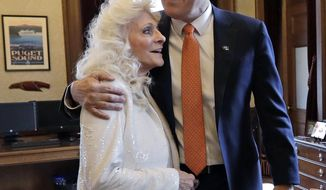 Washington Gov. Jay Inslee, center, embraces singer Judy Collins as they meet before his inaugural address to a joint session of the Legislature, Wednesday, Jan. 11, 2017, in Olympia, Wash. Collins sang the national anthem to open the inaugural event. (AP Photo/Elaine Thompson)