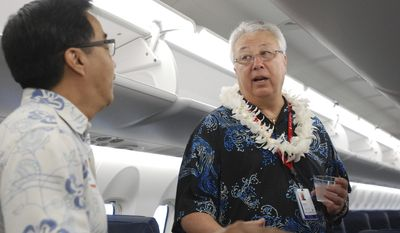 Island Air CEO David Uchiyama talks to a guest on board the airline's new Bombardier Q400 airplane before a blessing ceremony in Honolulu on Wednesday, Jan. 11, 2017. Island Air plans to start flying a faster, larger plane within Hawaii, putting it in a position to grab a bigger piece of the interisland market. (AP Photo/Audrey McAvoy)