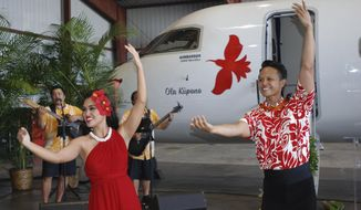 Hula dancers Kaui Perreira, left, and Kaimana Domingo perform during a ceremony to bless Island Air's new Bombardier Q400 airplane in Honolulu on Wednesday, Jan. 11, 2017. Island Air plans to start flying a faster, larger plane within Hawaii, putting it in a position to grab a bigger piece of the interisland market. (AP Photo/Audrey McAvoy)