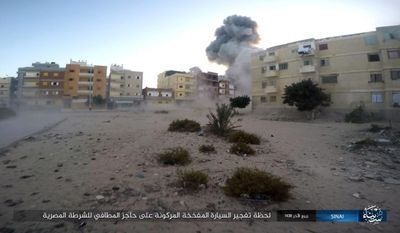 """This photo posted on a file sharing website Wednesday, Jan. 11, 2017, by the Islamic State Group in Sinai, a militant organization, shows an explosion as militants attack an Egyptian police checkpoint on Monday, Jan. 9, 2017, in el-Arish, north Sinai, Egypt. An Israeli defense official said Wednesday  that the country has developed a new policy in recent years to allow Egypt to quickly beef up its forces in the volatile Sinai peninsula as part of a shared struggle against Islamic militants. The comments came days after Egyptian President Abdel-Fatteh el-Sissi said there are about 25,000 Egyptian troops operating in Sinai. Arabic reads, """"The moment a car bomb explodes next to an Egyptian Police fire station checkpoint."""" (Islamic State Group in Sinai, via AP)"""