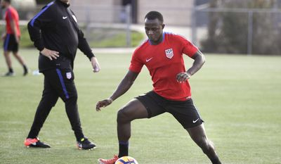 Kekuta Manneh dribbles the ball as U.S. men's national soccer team coach Bruce Arena, rear left, watches during a practice session Wednesday, Jan. 11, 2017, in Carson, Calif. Manneh has become a U.S. citizen, moving the Vancouver Whitecaps forward closer to eligibility for the men's national team. U.S. Soccer announced Manneh received his citizenship Wednesday, after the opening practice of January training camp under new coach Arena. (AP Photo/Jae C. Hong)