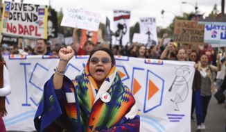 File - In this Jan. 2, 2017 file photo, protesters rally against the Dakota Access Pipeline behind the 128th Rose Parade in Pasadena, Calif. The front lines of the battle against the $3.8 billion Dakota Access pipeline are shifting away from the dwindling encampment in North Dakota. (AP Photo/Michael Owen Baker, File)