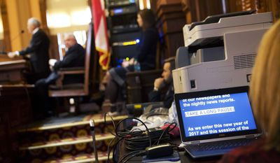"A computer monitor displays the speech of Georgia Gov. Nathan Deal, left, as he delivers the State of the State address on the House floor in Atlanta, Wednesday, Jan. 11, 2017. Deal is asking Georgia lawmakers to support a new plan for fixing low-performing schools after voters last fall rejected a proposal for state takeovers of schools that consistently struggle. The Republican governor said in his State of the State speech Wednesday that nearly 89,000 students were stuck in failing schools last year and their number ""will grow with each passing school year"" if nothing is done. (AP Photo/David Goldman)"