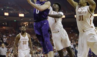 TCU guard Jaylen Fisher (0) scores past Texas defenders Andrew Jones (1) and Jarrett Allen (31) during the first half of an NCAA college basketball game, Wednesday, Jan. 11, 2017, in Austin, Texas. (AP Photo/Eric Gay)