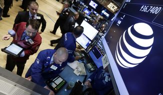 FILE - In this Monday, May 19, 2014, file photo, traders gather at the post that handles AT&T on the floor of the New York Stock Exchange. AT&T says the market for its new internet cable service, DirecTV Now, could be as large as 20 million households. (AP Photo/Richard Drew, File)