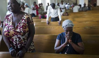 In this Thursday, Jan. 12, 2017 photo, residents attend a Mass during the 7th anniversary of the earthquake in Port-au-Prince, Haiti. Many Haitians lit candles and offered prayers Thursday to remember relatives and neighbors who died in a catastrophic earthquake that struck near the Caribbean nation's capital seven years ago.(AP Photo/Dieu Nalio Chery)