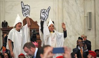 Protesters dressed as Ku Klux Klan members disrupt the Senate Judiciary Committee's confirmation hearing for Attorney General-designate Sen. Jeff Sessions on Tuesday. (Associated Press)