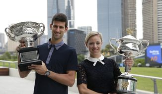 Defending men's and woman's champions Serbia's Novak Djokovic, left, and Germany's Angelique Kerber pose with their trophies prior to the official draw ceremony ahead of the Australian Open tennis championships in Melbourne, Australia, Friday, Jan. 13, 2017. (AP Photo/Mark Baker)